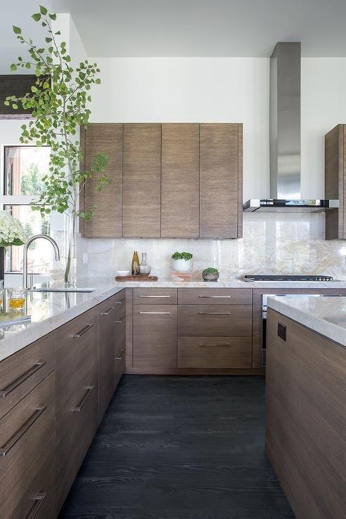 Dark wood cabinets in a white marble kitchen